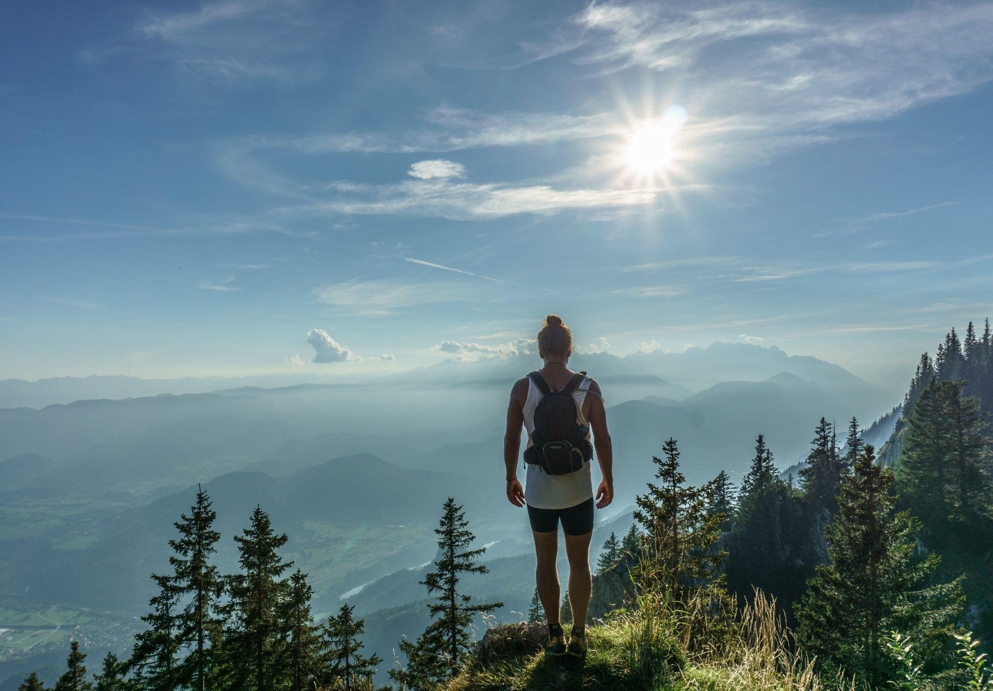 Foto van een man die uitkijkt over de bergen